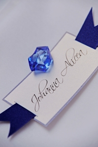 White place card with blue edges and cobalt blue grosgrain ribbon and blue seaglass for Miami wedding