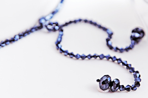 Blue swarovski strand with end tassels on white wedding cake for Miami wedding