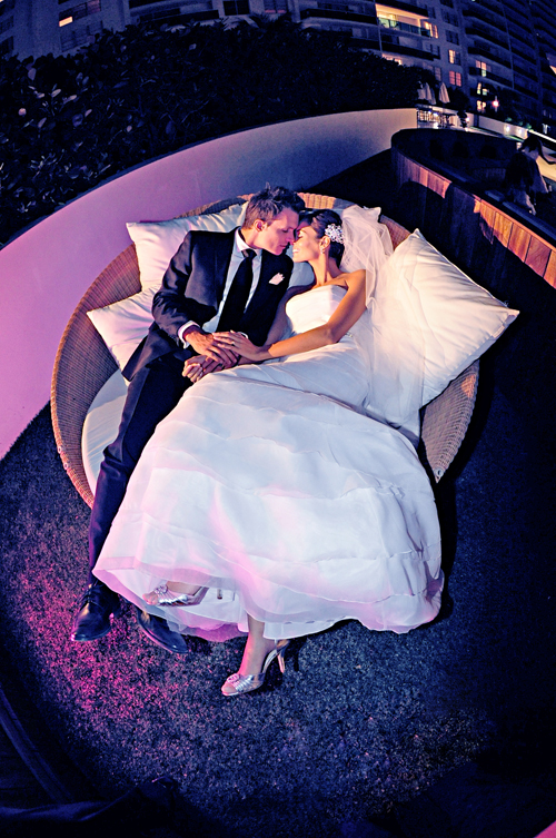 Joan Montanez and Chad Love, bride and groom on round couch at Miami wedding reception.